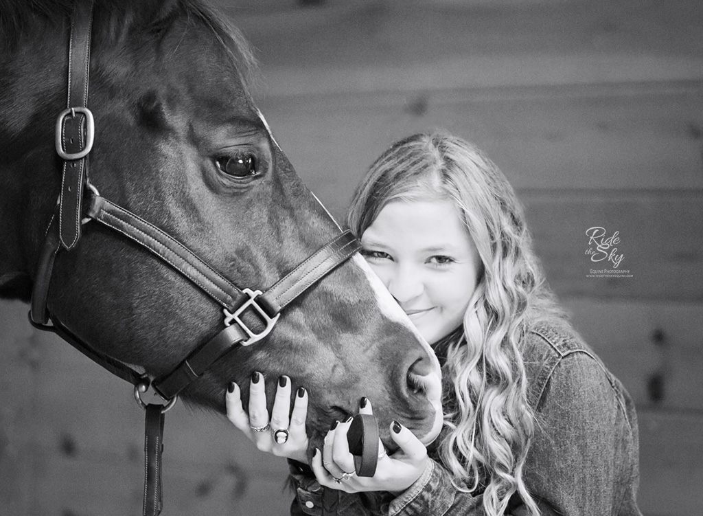 Girl smiling while holding Horse's face in Black and White