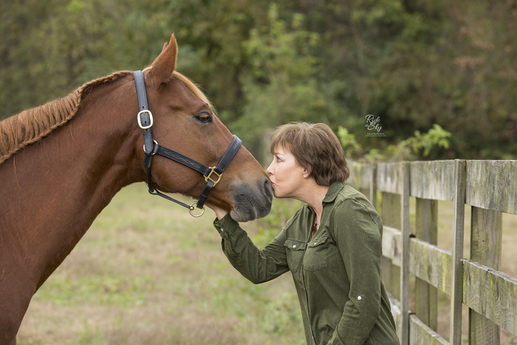 Woman kissing horse muzzle in fall field