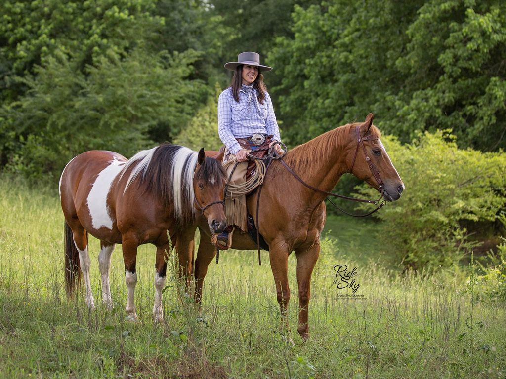 Cowgirl and two horses in green field