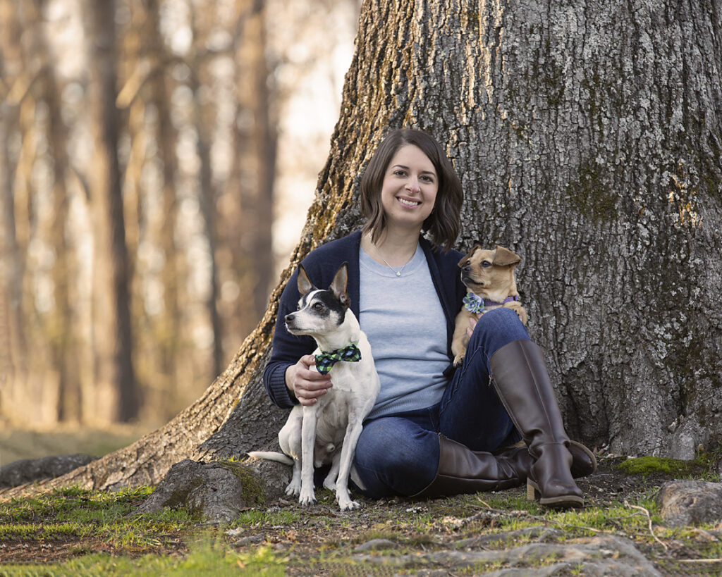 Woman and two dogs sitting next to tree at Nature Park in February