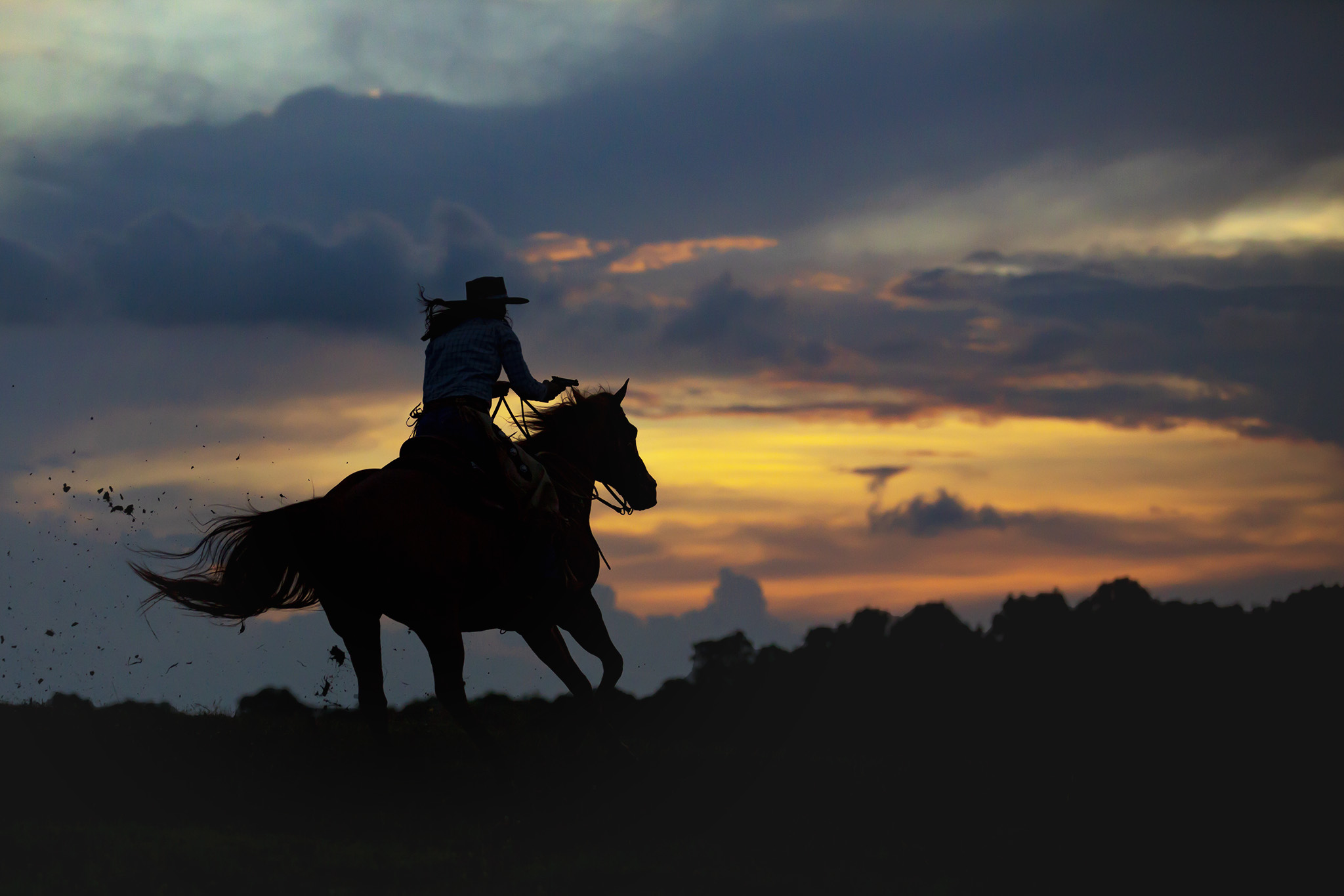 Commercial Equestrian Lifestyle image of cowgirl riding horse at sunset