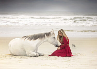 Girl in red dress connecting with horse laying down on beach