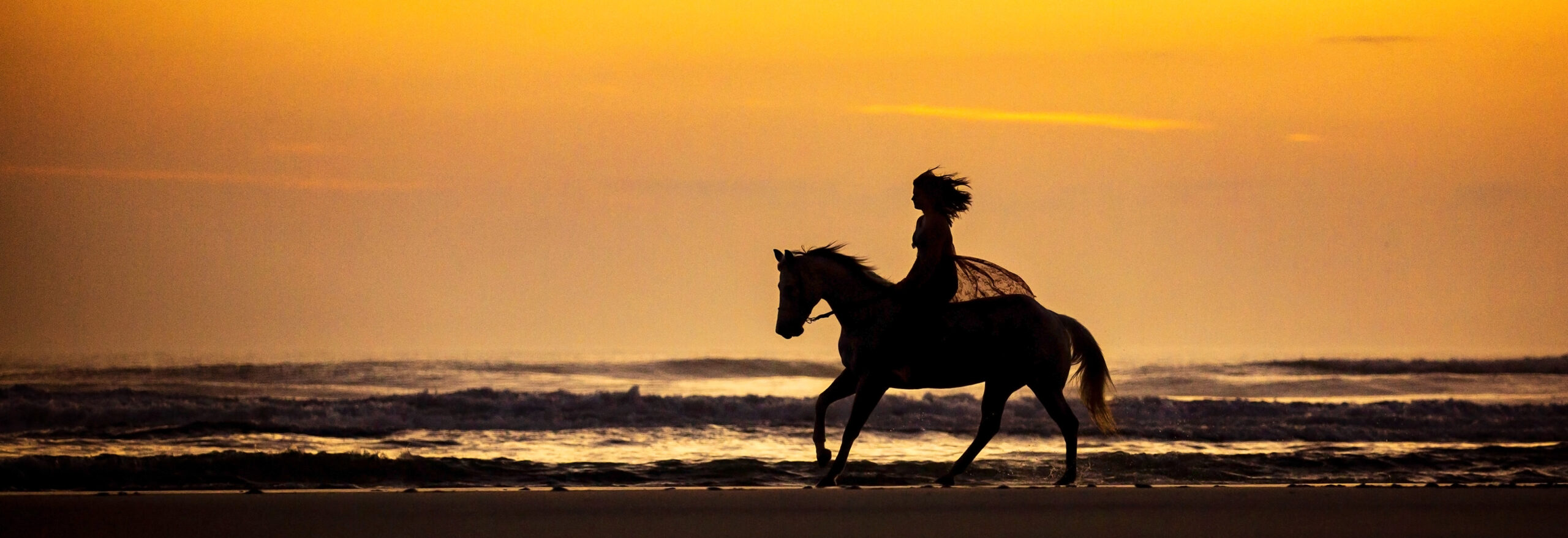 Woman Riding Horse on Beach at Sunrise
