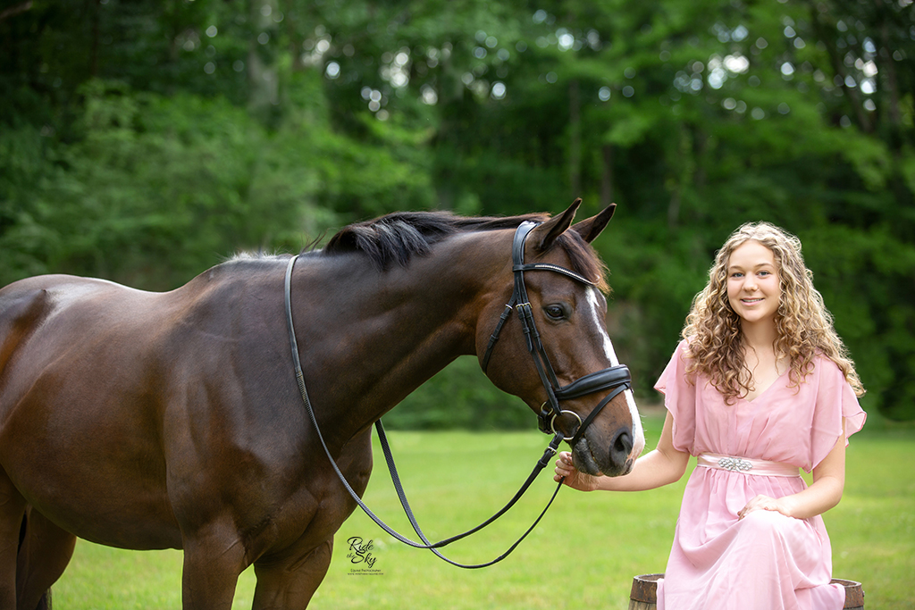 Girl on whiskey barrel in field with horse