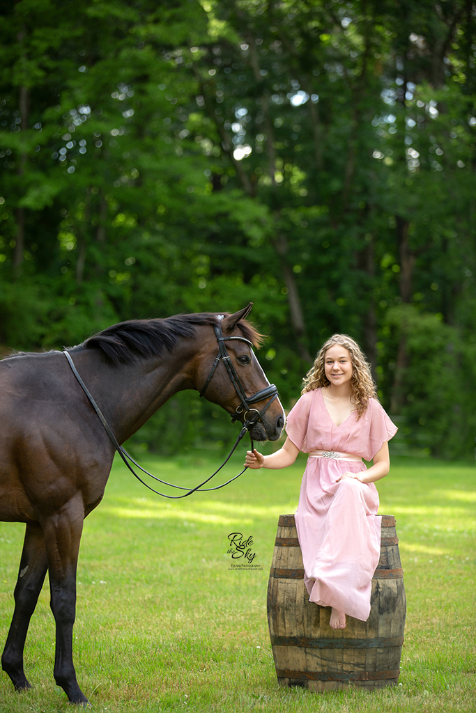Girl in pink dress sitting on whiskey barrel next to horse