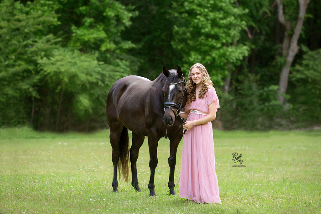 Girl in pink dress with thoroughbred horse
