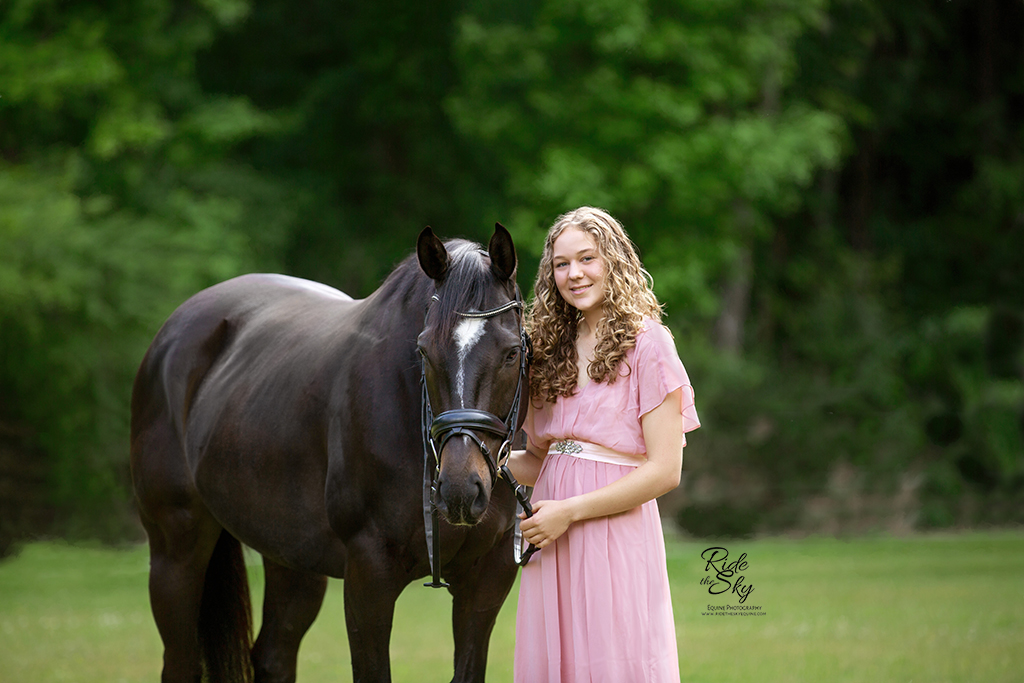 Girl in pink dress with thoroughbred horse in field