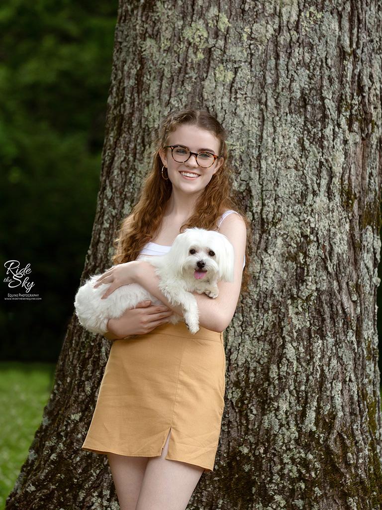 Girl leaning on tree holding dog