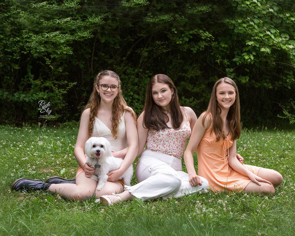 Three teenage girls sitting on ground in nature park in summer with white dog