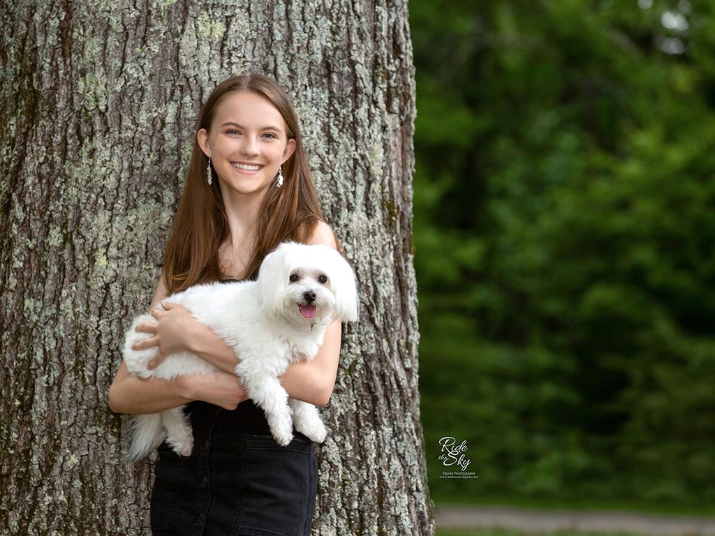 Girl leaning on tree holding white dog