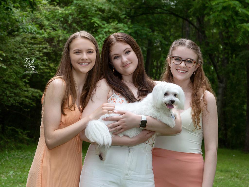 Three teenage girls holding white dog in Enterprise South Nature park